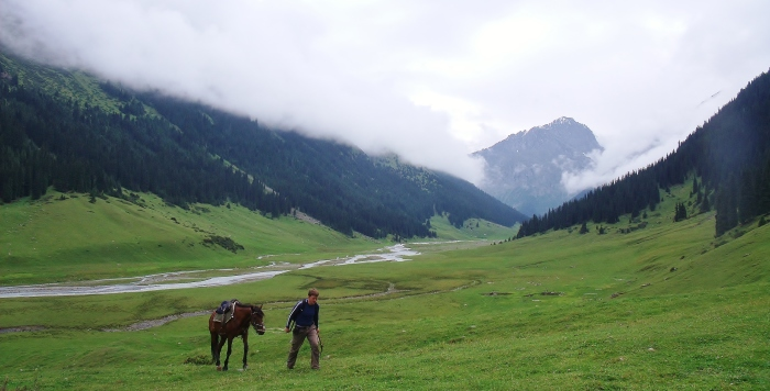 I walk with my horse through the mountains, near Altyn Arashan in Kyrgyzstan.