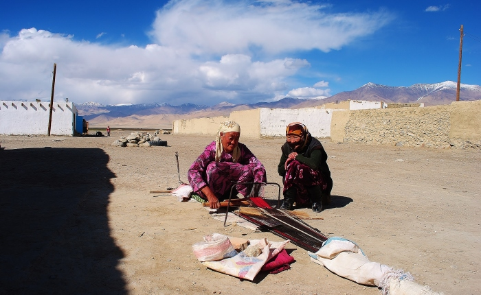 Women sewing a blanket in the Pamir Highway.