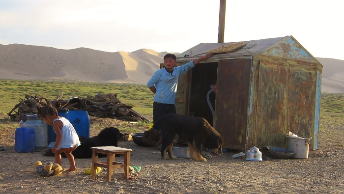 The Gobi desert - Mongolian family at the background of Khongorun Els sand dunes.