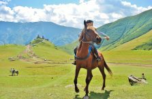 Gruzja - chłopiec na koniu na tle kościoła Tsminda Sameba.