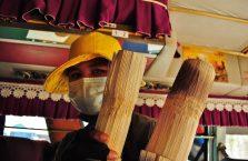 Kambodża - kobieta w masce sprzedaje ryż w bambusach.