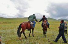 Kirgistan - ludzie na koniach nad jeziorem Song-Kol.